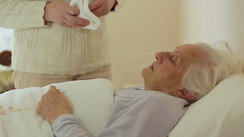old wrinkled woman laying in bed: assistance, illness, sickness, disease
