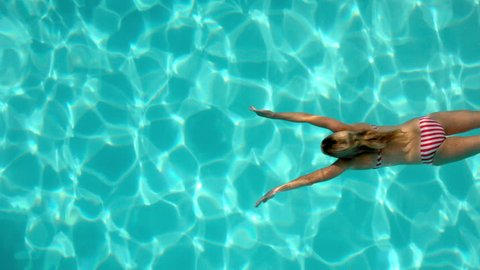 Woman swimming in the pool underwater overhead in slow motion