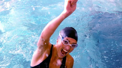 Fit Caucasian swimmer jumping up and cheering in the pool in slow motion
