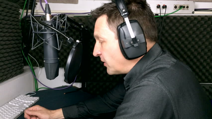 A voiceover artist recording a voiceover for a tv commercial in a voiceover booth at a recording studio.