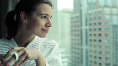 Beautiful woman drinking coffee by the window with cityscape view