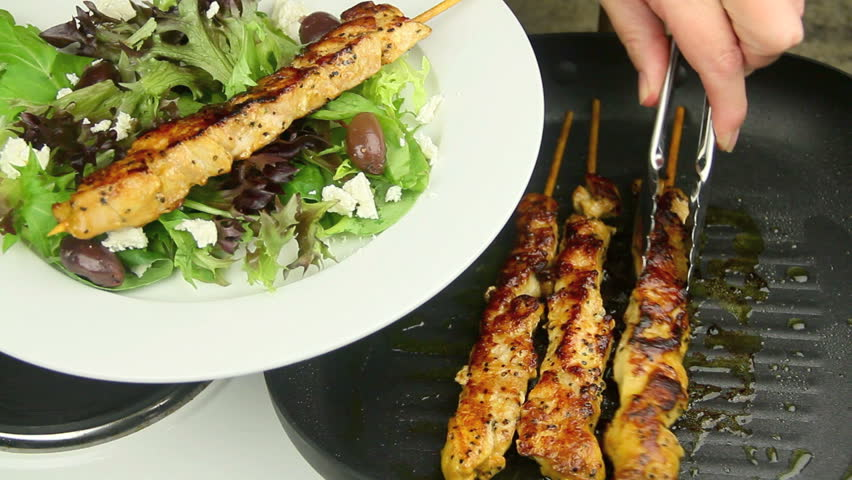 Grilled chicken kabobs being served from a griddle pan with tongs on to a plate with salad.  #6582203