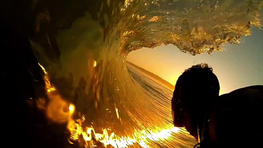 High contrast POV shot of silhouetted surfer as he rides through the barrel of a dark orange wave, with the sun setting ahead of him | Shutterstock Video #6596987