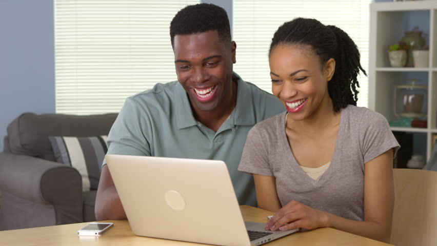 Happy young black couple laughing and using laptop together | Shutterstock HD Video #6645830