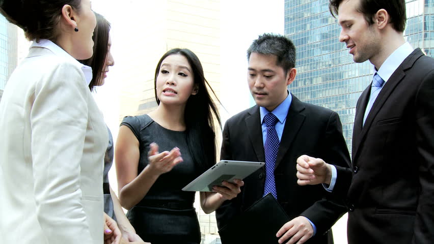 Confident young male female multi ethnic business colleagues meeting talking spreadsheet data online wireless technology outside downtown office building | Shutterstock HD Video #6646751