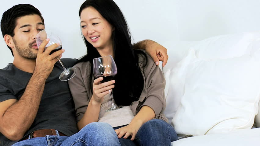 Casually dressed young Asian Chinese couple enjoying time together talking  drinking glass wine home sofa slow