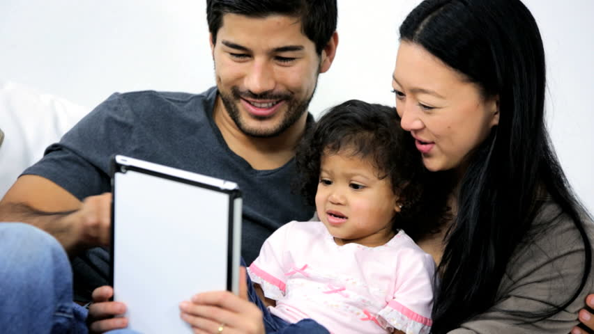 Close up smiling Asian Chinese parents sitting home sofa cute young daughter having fun together using modern touch screen tablet technology | Shutterstock HD Video #6657212