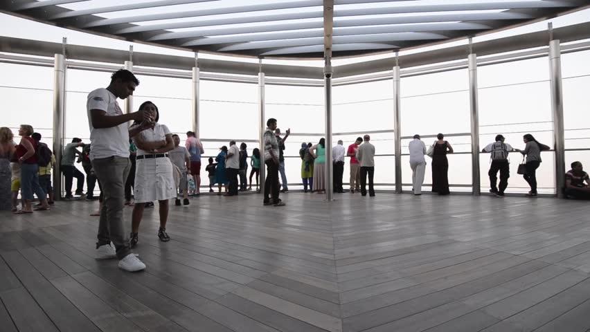 DUBAI, UAE - MARCH 30, 2014: People walking on Burj Khalifa observation terrace. Burj Khalifa is the tallest man-made structure in the world, at 829.8 m (2,722 ft).  | Shutterstock HD Video #6658994