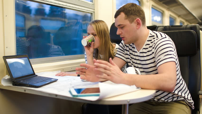 Young man and woman working with plan during their trip in the train. Woman drinking tea or coffee. Working atmosphere with laptop and pad on the table | Shutterstock HD Video #6678662