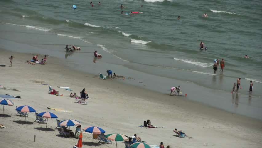 People Enjoying the Beach with Ocean Waves - HD stock video clip