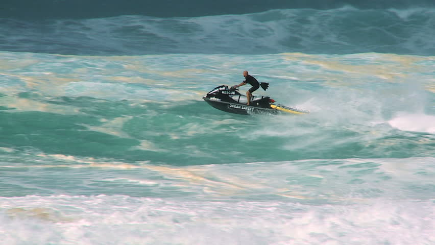 Dramatic shot of lifeguard on rescue jet-ski being hidden by crashing giant waves 60 FPS