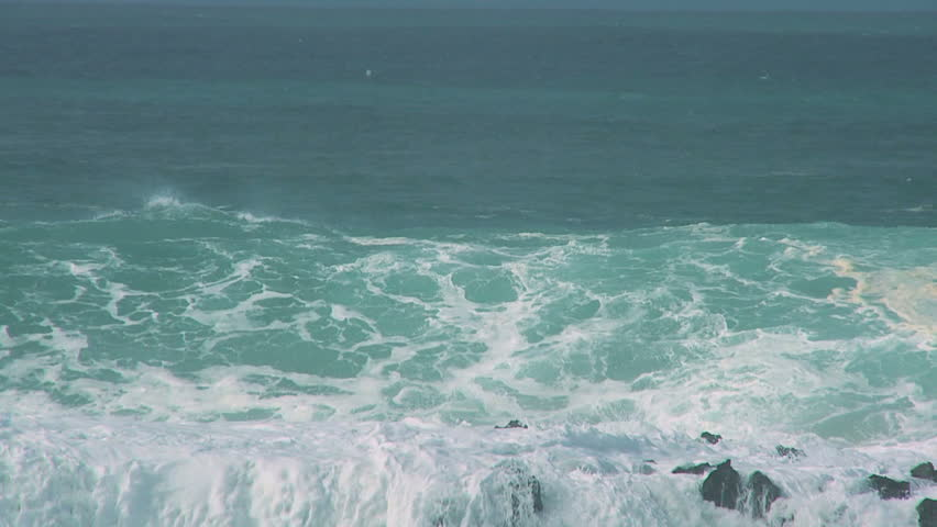 Giant breaking waves driven by high winds crashing over rocks 60 FPS