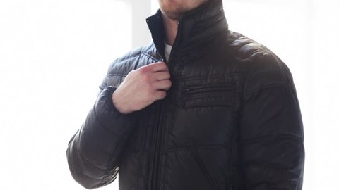 clothes, fashion and dressing concept - close up man unzipping his black jacket at home