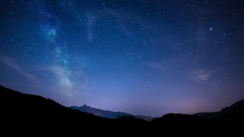 Timelapse night sky stars milky way on mountains background. 4K. Tuscany