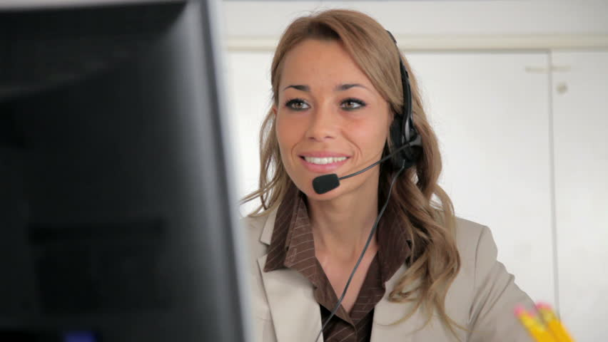Female receptionist working on computer and talking on the telephone in call center. Sequence