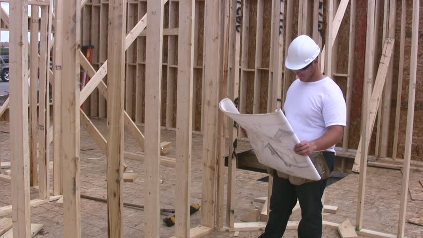 Construction Worker Checking The Plans To A New Building