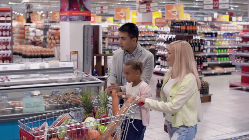 Family of three going to cash till, daughter riding the full shopping cart | Shutterstock HD Video #6823246
