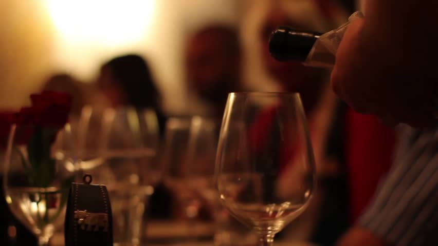 Waitress pouring red wine into glass
