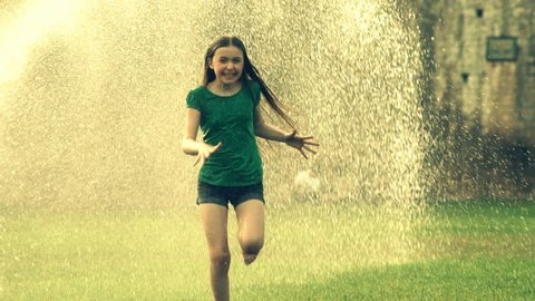 Slow motion of little girl running joyfully through a water sprinkler getting soaked on a hot summers day