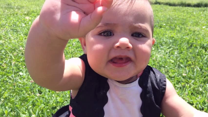 Cute little girl sitting in grass | Shutterstock HD Video #6869770
