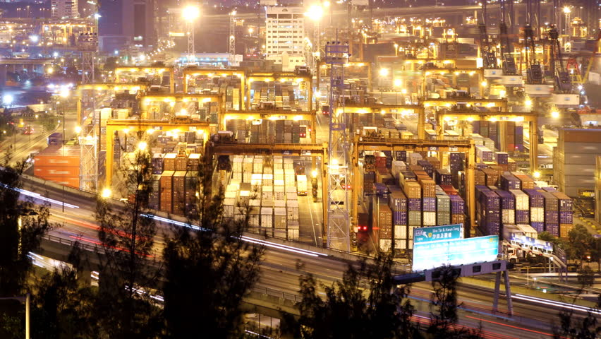 Cargo Container Loading Activity. Timelapse at night. Wide shot. Slowly zooming in. Busy traffice on highway at the front.