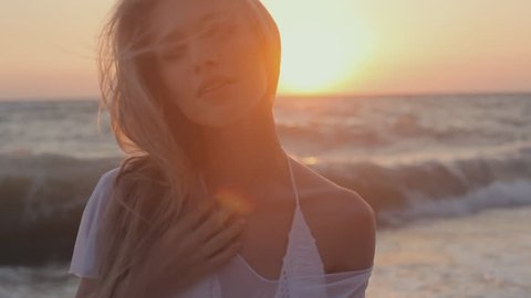 Seductive girl with long hair dressed in a transparent tunic posing at sunset on the beach