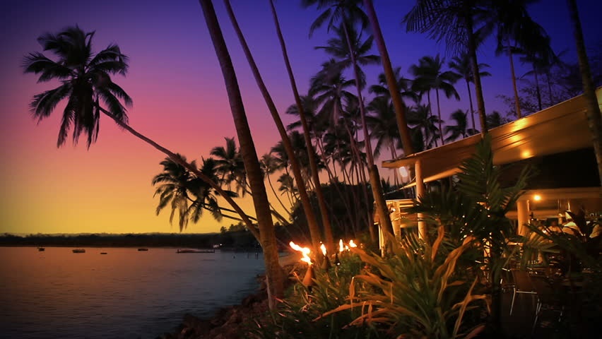 Beach-side restaurant / cafe / bar lit by flaming torches, at sunset in tropical Fiji. Idyllic romantic summer night dining under a purple sky.