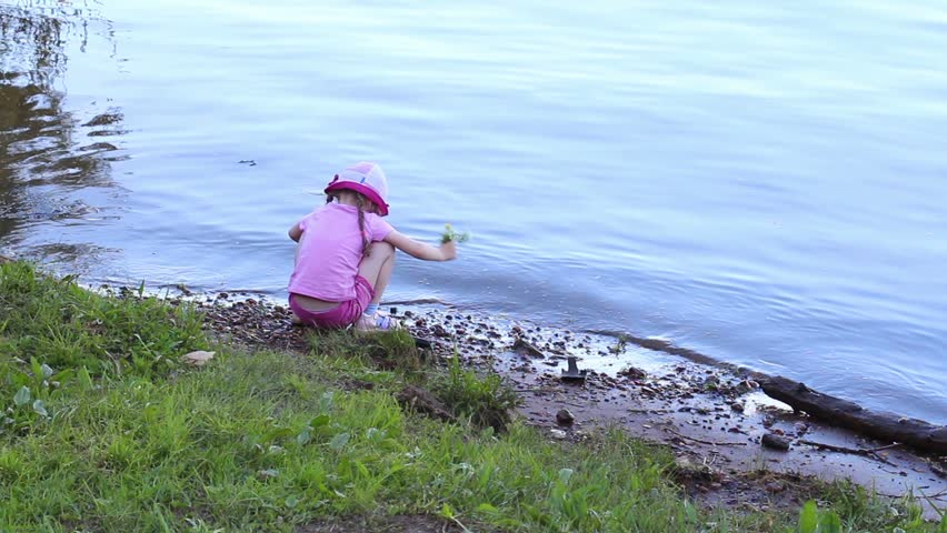 Back of little cute girl in pink sitting on shore of river and looking at water 