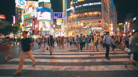 TOKYO - JAPAN, MAY 25, 2014: People crossing the street outside the famously crowded Shibuya station from point of view (POV) perspective, Tokyo, Japan.
