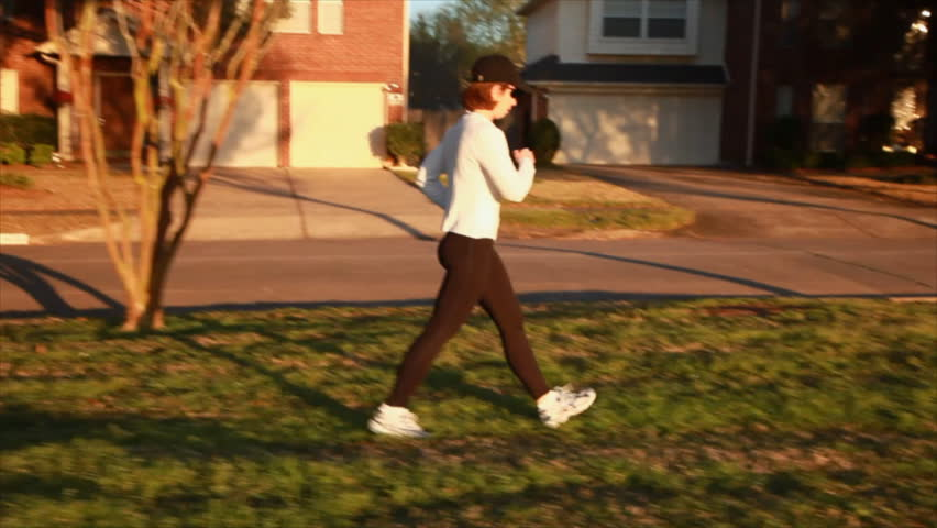 A woman enjoying a brisk morning walk in a neighborhood park area. | Shutterstock HD Video #699040