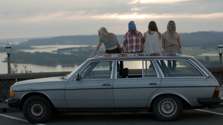 Friends Sit On Roof Of Car, Watch The Sun Go Down At  Epic Viewpoint, Girl Rests Her Head On Friend's Shoulder  #6991210