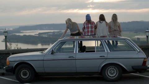 Friends Sit On Roof Of Car, Watch The Sun Go Down At  Epic Viewpoint, Girl Rests Her Head On Friend's Shoulder