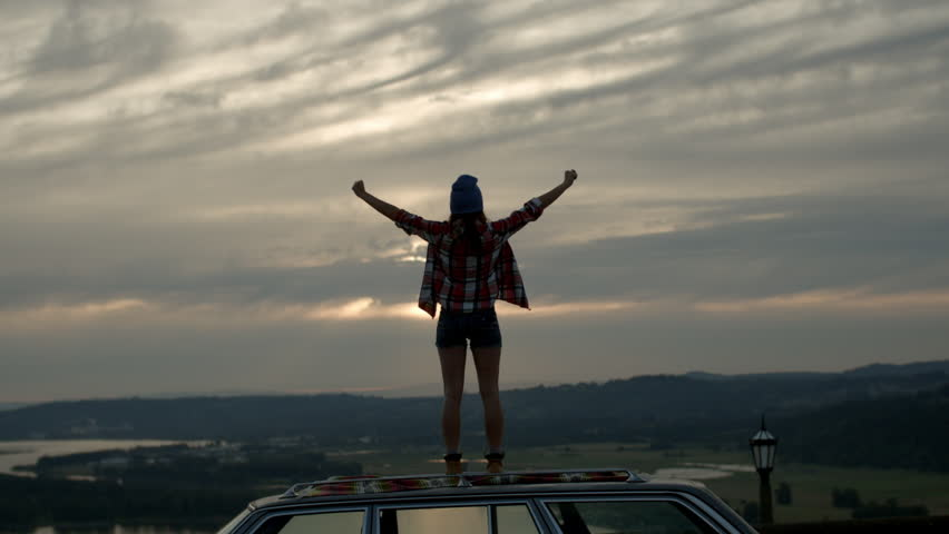 Young Woman Stands On Her Car And Takes In The Surrounding Beauty, She Raises Her Arms And Jumps Up And Down In Awe Of The View #7000630