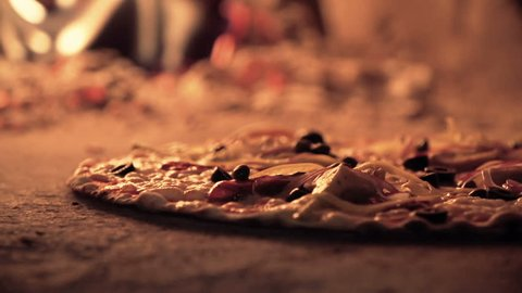 Extreme close up of pizza bubbling in the masonry oven and taken out when ready