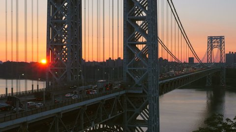 The sun rises as morning rush hour traffic on the George Washington Bridge crosses the Hudson River between New Jersey and New York.