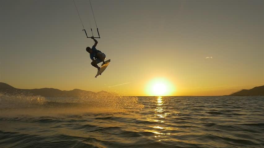 SLOW MOTION: Kiteboarder jumping at golden sunset