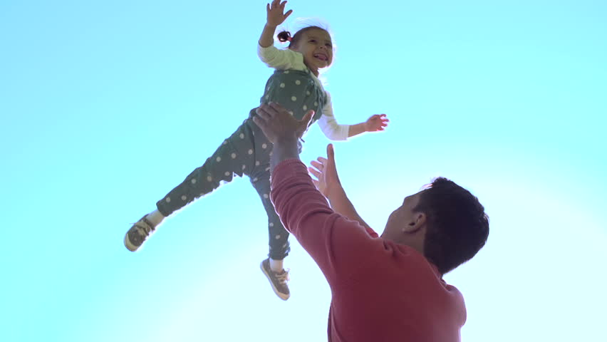 Slow motion of handsome father throwing his adorable daughter in the air