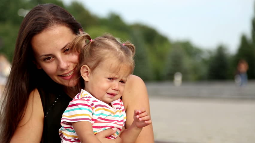 Portrait of a young mother with a child.Young mother on a walk in the city. | Shutterstock HD Video #7215310