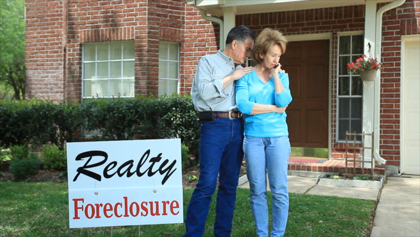 A distressed couple, standing behind a foreclosure sign in their front yard.