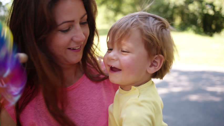 Mother and son play with pinwheel in park | Shutterstock HD Video #7245778