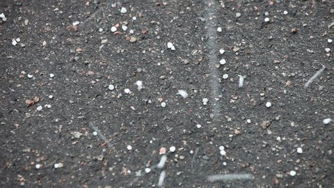 White hailstones bouncing off black asphalt during a hail storm
