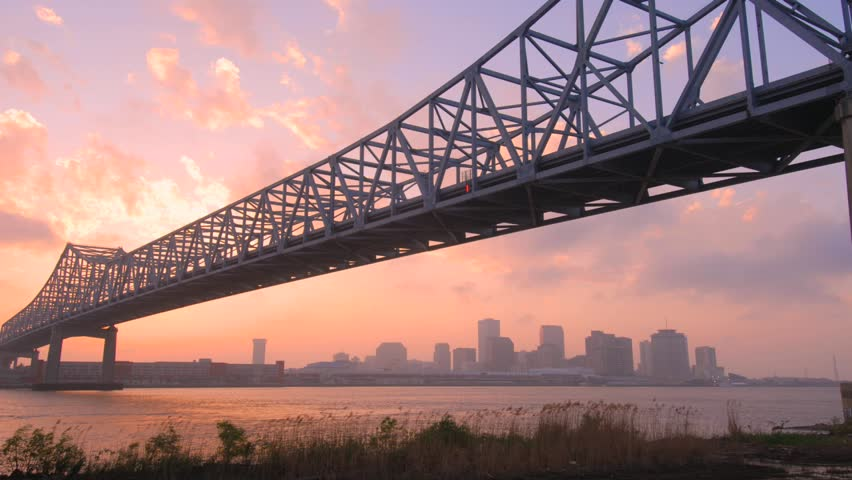 Time lapse of New Orleans skyline during sunset with Mississippi River and bridge in foreground.