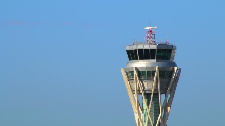 Barcelona Airport Control Tower. Airport control tower at full capacity. Radar control tower with an airplane across the sky.