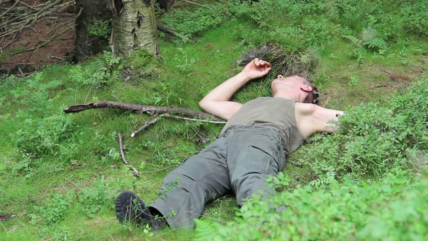 Dead, sick or drunk man lies on the ground in the mountains forest.