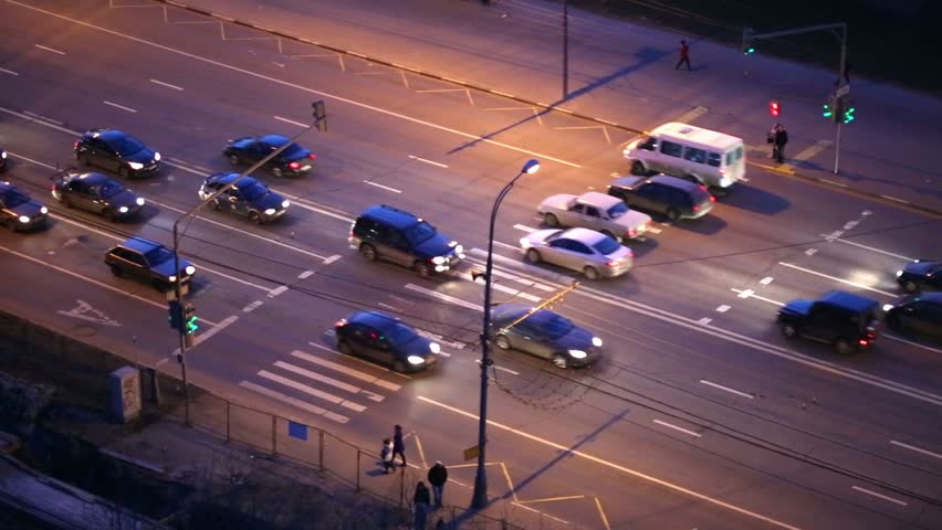 People Cross Road At Zebra Crossing While Cars Stop In Front Of