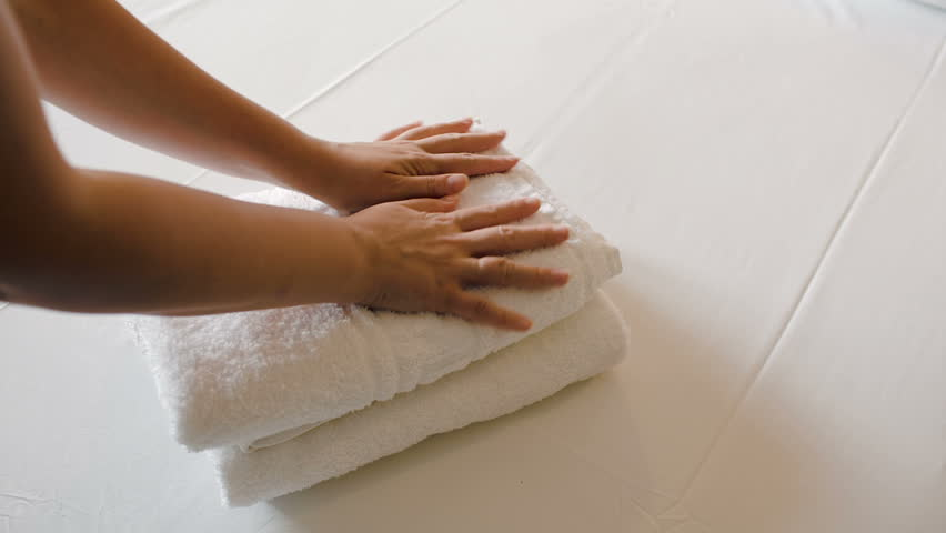 Close-up shot of woman putting two fresh clean towels on the bed with white sheet