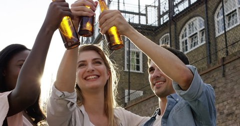 Friends celebrating drinking beer lifting arms summer outdoors