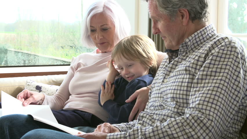 Grandparents With Grandson Reading Book On Sofa
