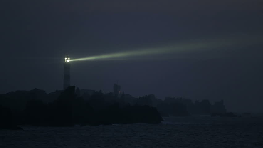 Creach lighthouse illuminated in evening along the rocky shore, the most powerful in the world, Ushant island (aka Ouessant), Brittany, France