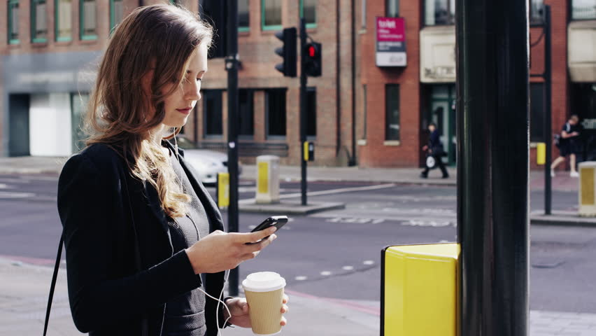 Attractive business woman commuter using smartphone walking in city of london - RED EPIC DRAGON 6K